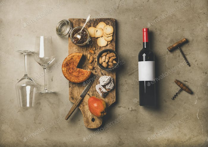 Wine bottle, vintage corkscrews, wineglasses and appetizers board, top view