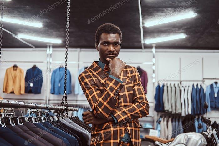 Элегантно одетый африканский мужчина позирует с рукой на подбородке, стоя в классическом магазине мужской одежды.