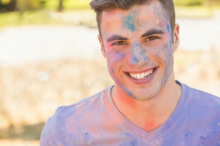 Young man having fun with powder paint on a sunny day