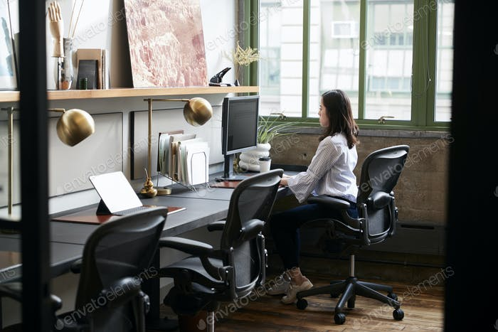 Young woman working alone in a compact office