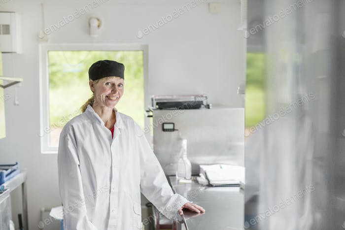 Portrait of woman wearing white coat in commercial kitchen