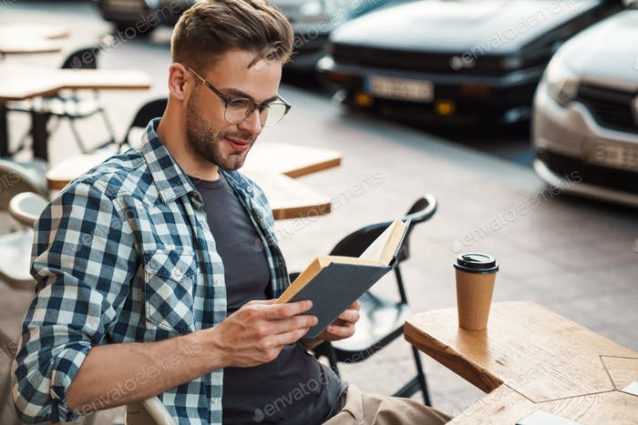 Happy man enjoying free time and reading a book