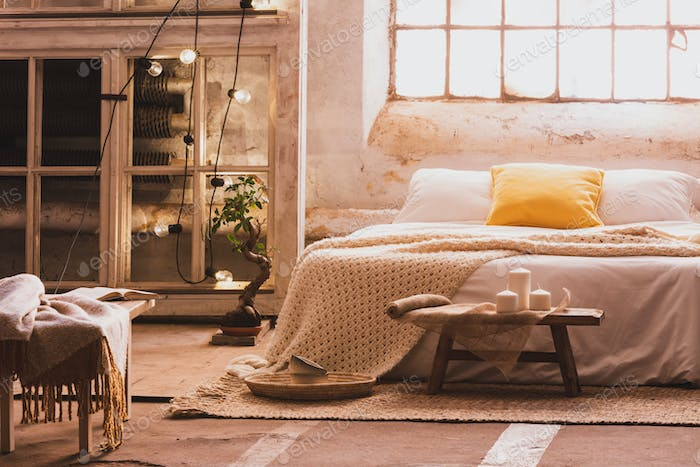 Cozy bedroom interior with a bed, stool, candles and industrial