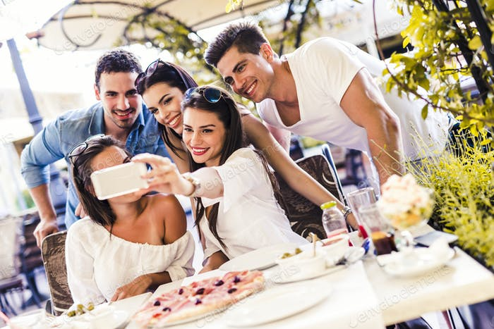 Group of young beautiful people sitting in a restaurant and taki