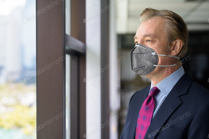 Mature businessman thinking and looking outside the window with mask for protection from corona