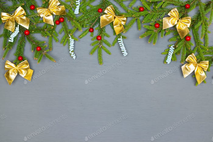 Decorated natural green Christmas tree branches on gray painted wood