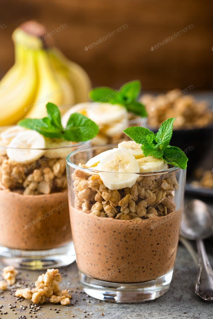 Layered chocolate chia pudding parfait with banana, granola and yogurt, dessert