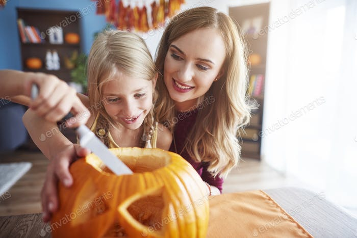 Mother and daughter making carved pumpkin