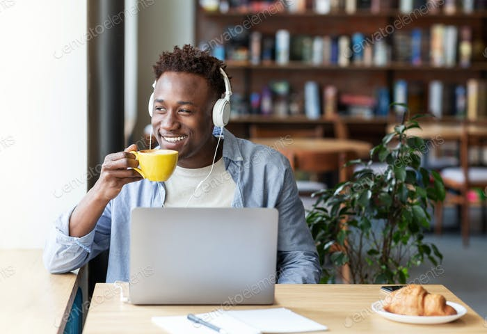 Happy black guy with headphones listening to music and drinking aromatic coffee at cozy cafe, empty