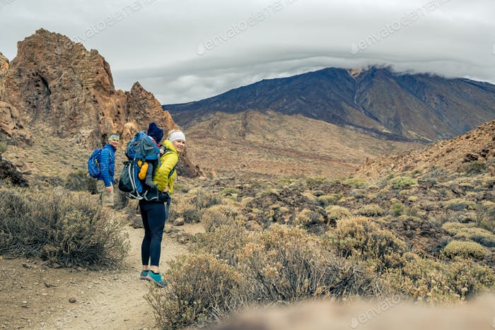 Family hiking with baby boy travelling in backpack