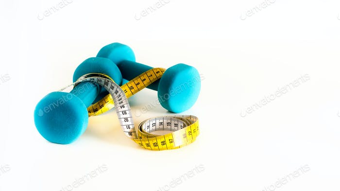 Fitness concept. Turquoise dumbbells and yellow measuring tape. Copyspace