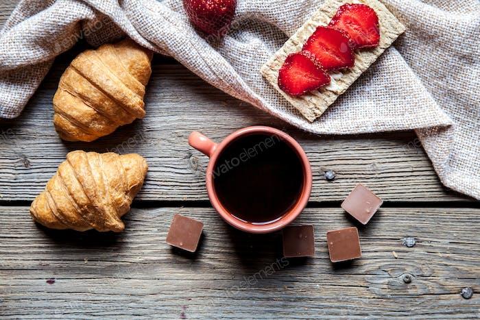 leckeres Frühstück mit einer Tasse Kaffee und Obst-Sandwiches, Croissants. Erdbeeren, Lebensmittel