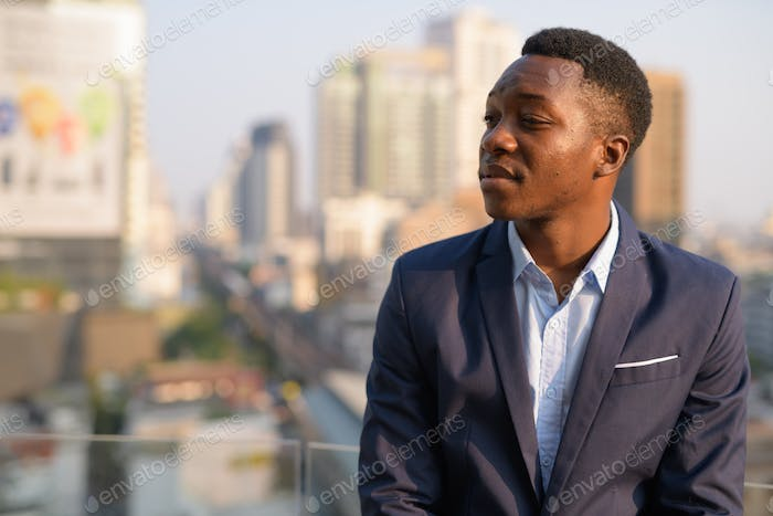 Face of young handsome African businessman thinking against view of the city