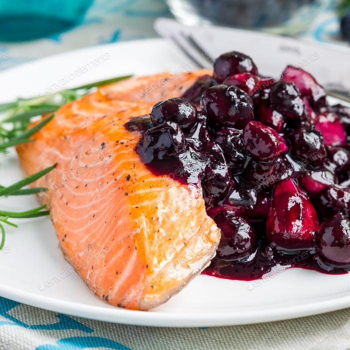 Baked salmon fillet with blueberry and rosmarin sauce on white plate, square format