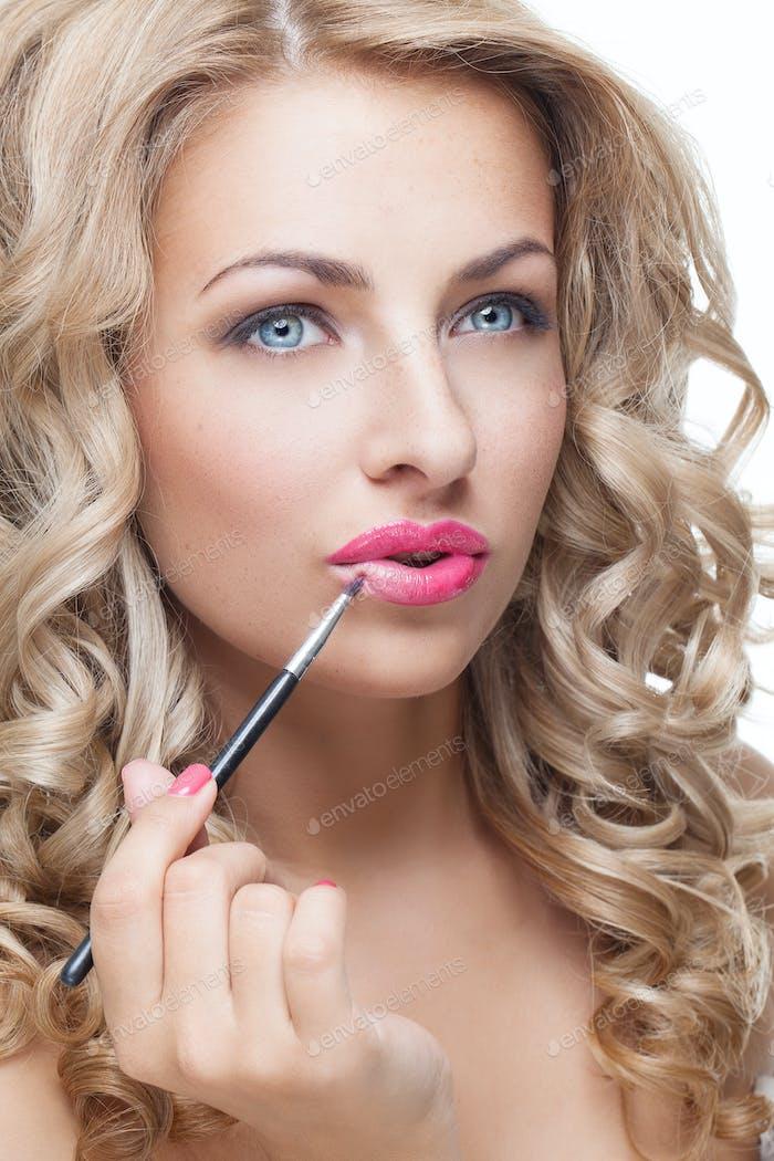 Beautiful girl putting lipstick on
