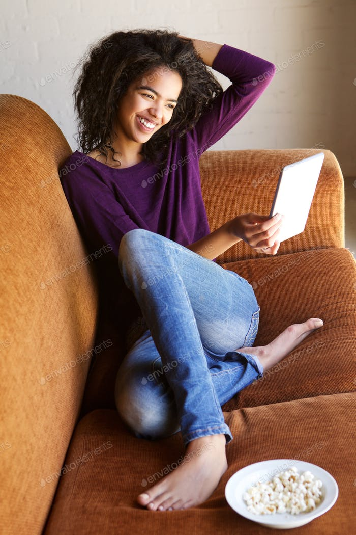 Smiling mixed race girl with digital tablet at home