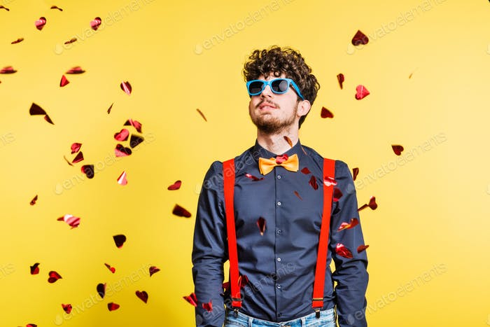 Portrait of a young man with sunglasses in a studio on a yellow background.