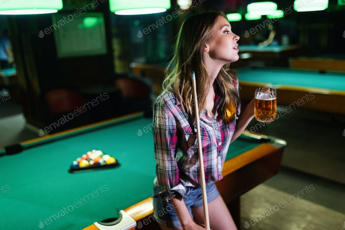 Young happy girl having fun with billiard. Play and fun concept