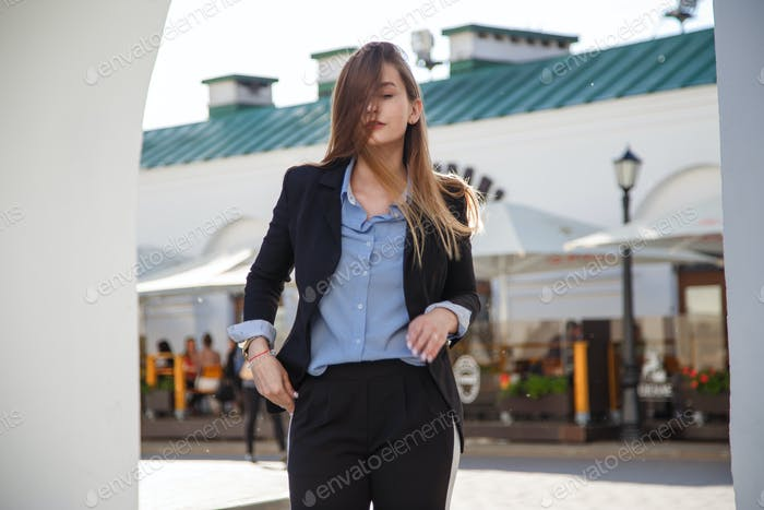 Fashionable women's look with black jacket and blue blouse.