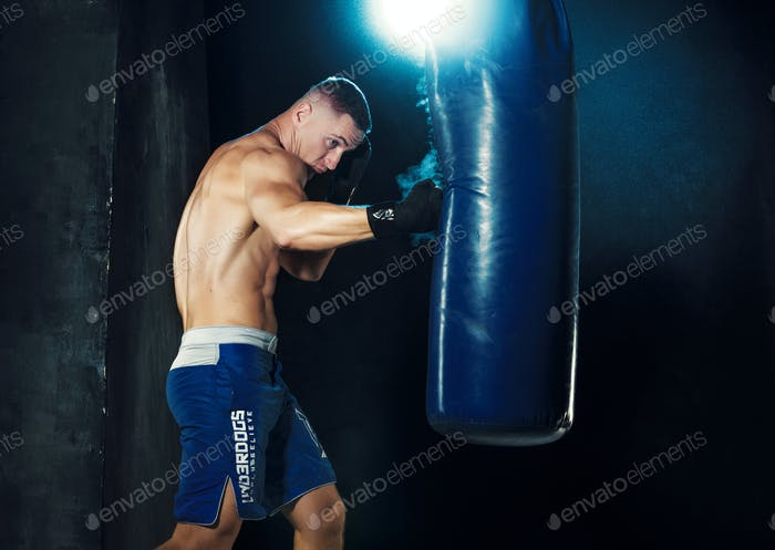 Male boxer boxing in punching bag with dramatic edgy lighting in a dark studio