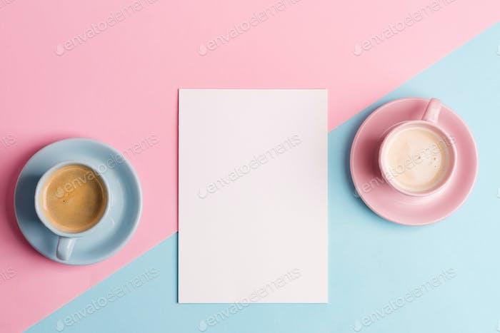 Kreative Pastellblau rosa Hintergrund mit zwei Keramiktassen frisch gebrühtem Kaffeegetränk und Papier