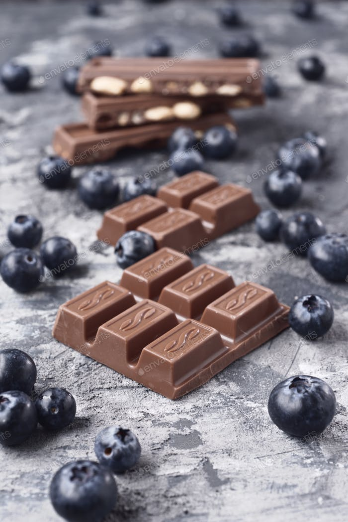 pieces of chocolate with blueberries on gray marbled textured background