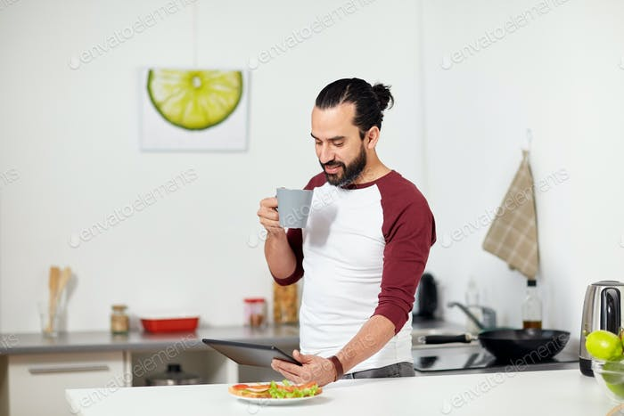 man with tablet pc eating at home kitchen