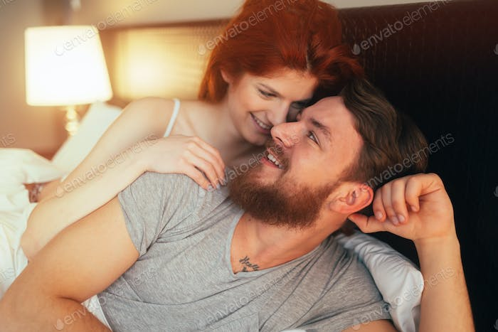 Happy couple in bed showing emotions