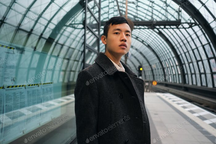 Young Asian businessman in coat intently looking in camera waiting train at subway station