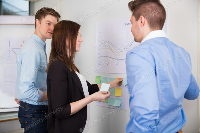 Businesswoman Sticking Adhesive Notes While Standing By Colleagu