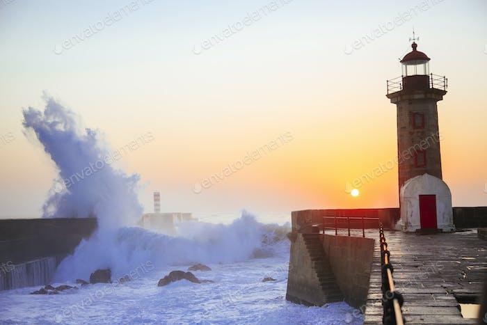 Lighthouse Felgueirasin Porto with wave splash at sunset, Porto, Portugal