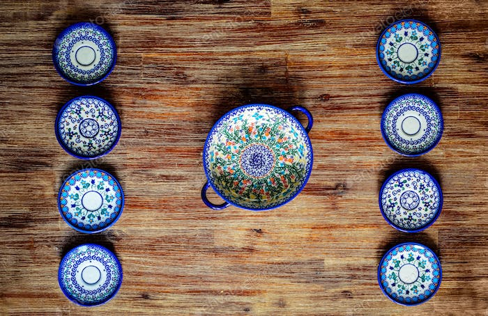 Detail of painted ornate pottery plates on wooden textured table in vintage style