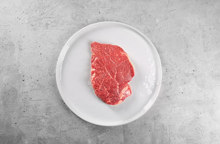 Raw beef steak on a white plate, top view