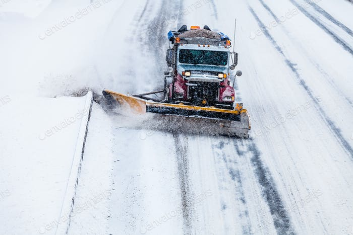 Snowplow removing the Snow from the Highway during a Snowstorm