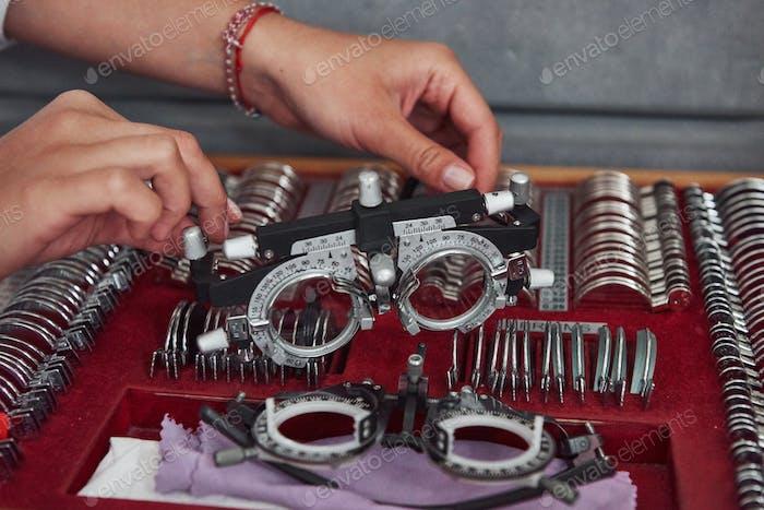 Ersatzteile unten. Weibliche Hände halten das optische Gerät für Augentests