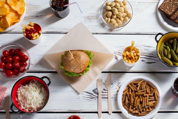 Burger und Chips mit Gurken.