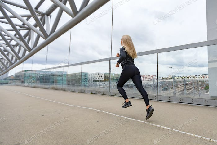 Fast running sporty woman in black workout outfit in modern city environment