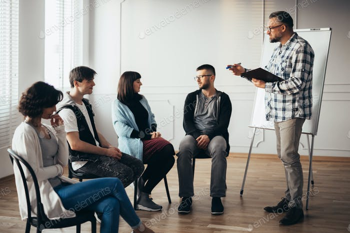 therapist stands in front of a group of people of different ages during meeting for people