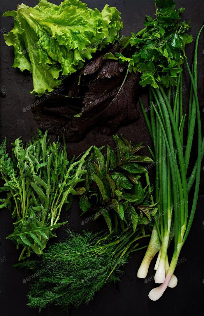 Variety fresh organic herbs on black background in rustic style. Top view