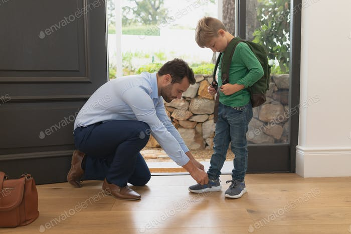 Side view of Caucasian father tying his sons shoelaces in a comfortable home