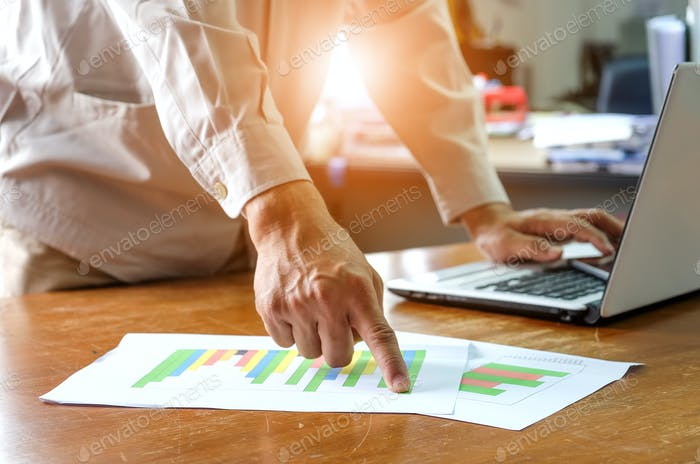 Business,Man working office are analyzing graph data with using