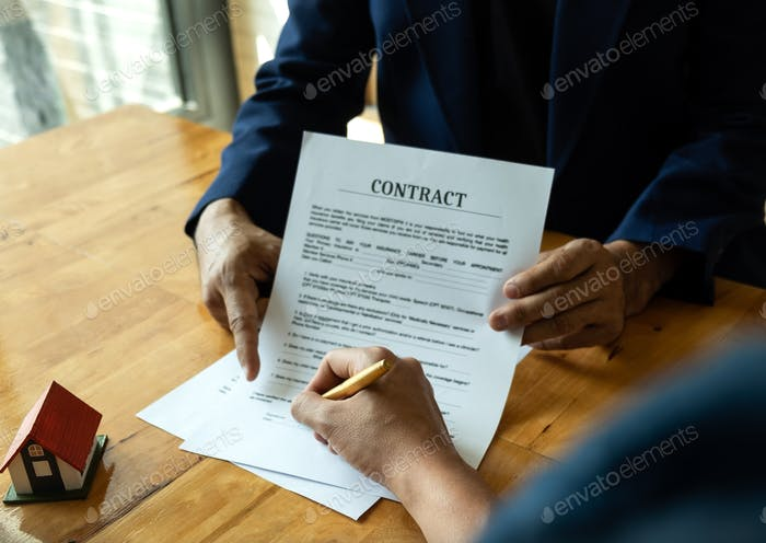 Businessmen point to documents for customers to sign.