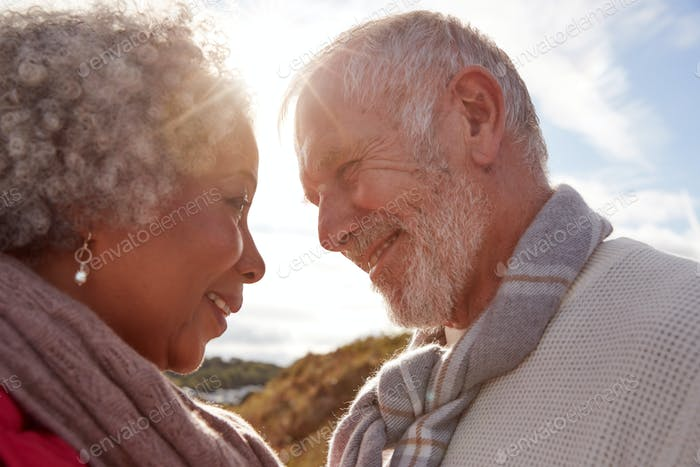 Head To Head Shot Of Loving Senior Couple Walking Outdoors Against Flaring Sun