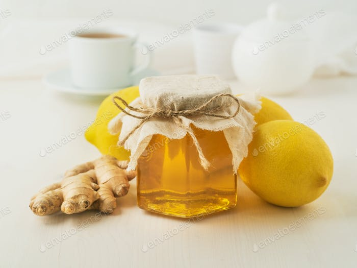 Popular ways to treat a cold - a jar of honey, ginger, lemons on white background, side view
