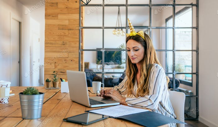 Business woman with unicorn headband working