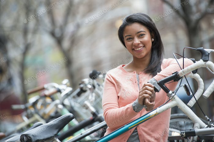 A young woman in a city park, standing beside a rack of parked locked bicycles.