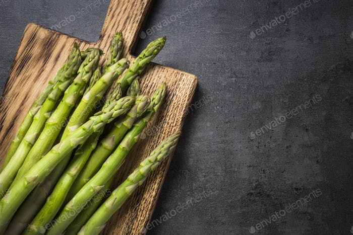 Fresh green asparagus on black slate background