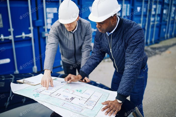 Two engineers discussing blueprints together in a shipping yard