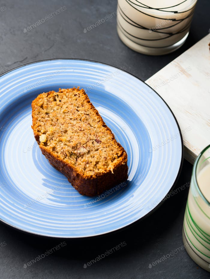 Banana bread loaf sliced on wooden board