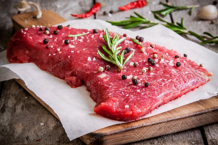 raw meat steak on a cutting board with rosemary and red pepper